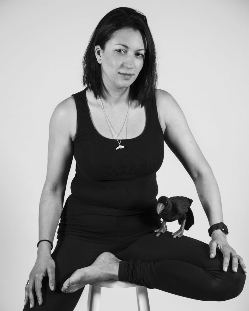 A woman sitting on a stool wearing all black. She has dark straight hair and a crow on her lap